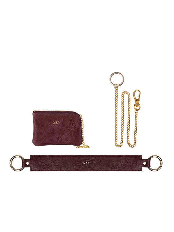 Small purple wallet with gold details, gold plated key chain and a purple wide strap with gold details