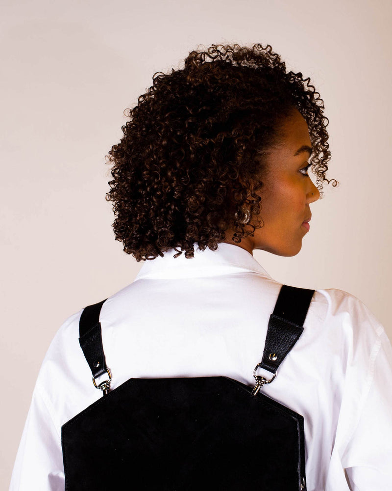 Two black shoulder straps with gold details on black backpack