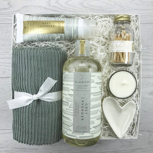 Gift box for housewarming and hostess.  Collection contains ripple tea towel, Illume Collectiv Grey Lavender dish soap, Grey Lavender hand cream, soy candle, heart shaped ring dish and Skeem white apothecary bottle of matches.