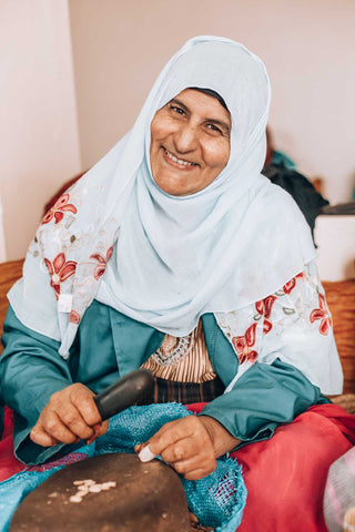 Berber woman smiling whilst working at the argan cooperative, cracking argan nuts in the making of argan oil