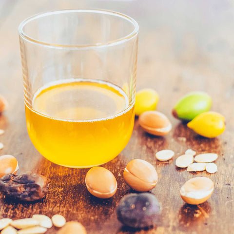 Vegan, all natural, culinary argan oil in a glass on a table with argan fruit, nuts and kernels