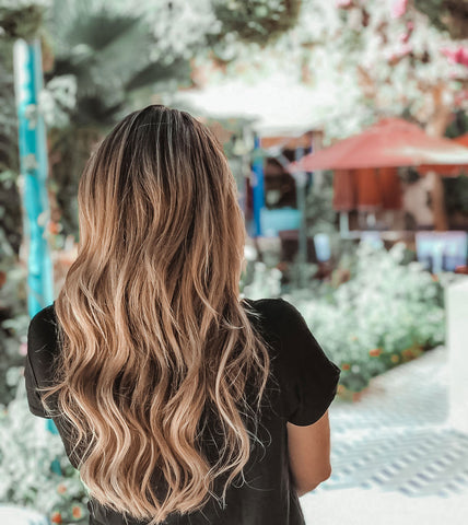 Women with her back turned showing her beautiful wavy hair, no longer frizzy thanks to her argan oil treatment