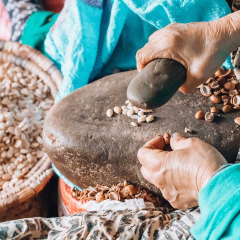 Moroccan woman cracking the argan nut on a stone, at the cooperative where youforher source their organic argan oil