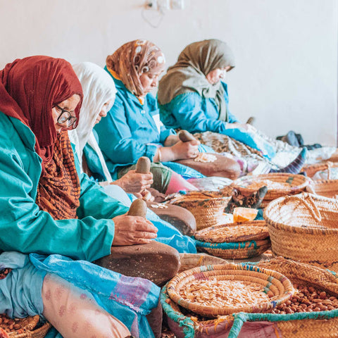 Women in the Moroccan argan oil cooperative cracking the argan nuts, in the process to extract argan oil