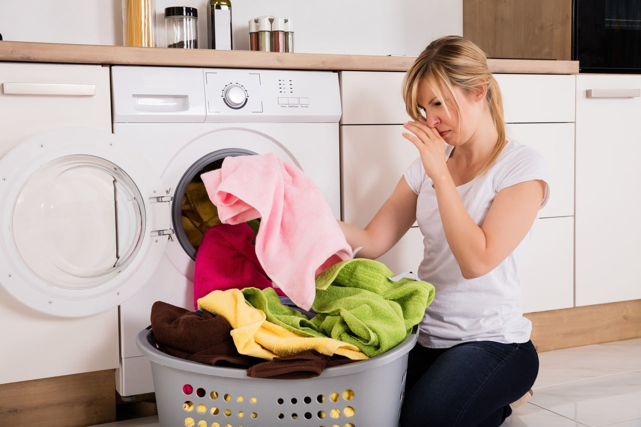 a woman who is uncomfortable because of the bad smell of towels in the laundry basket in front of the washing machine