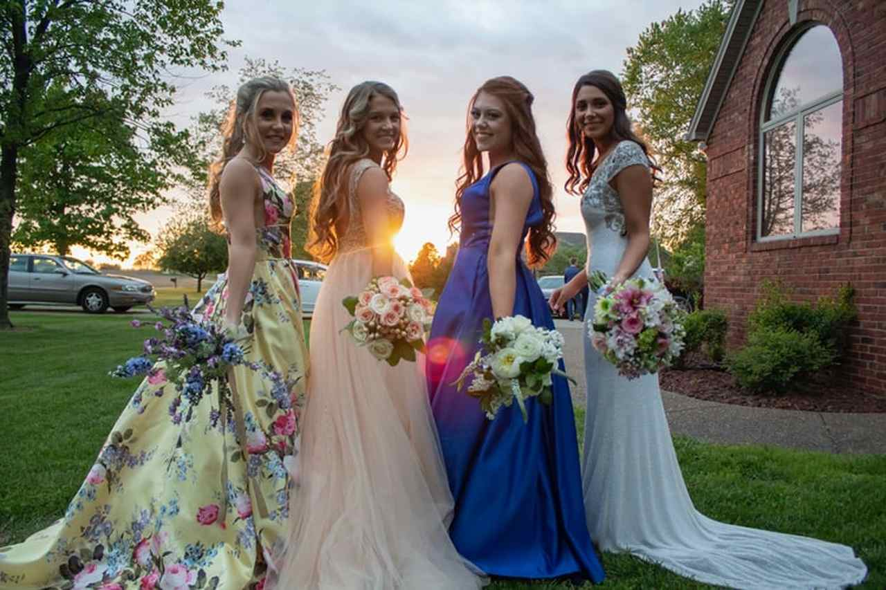 4 fancy bridesmaids holding flower bouqets