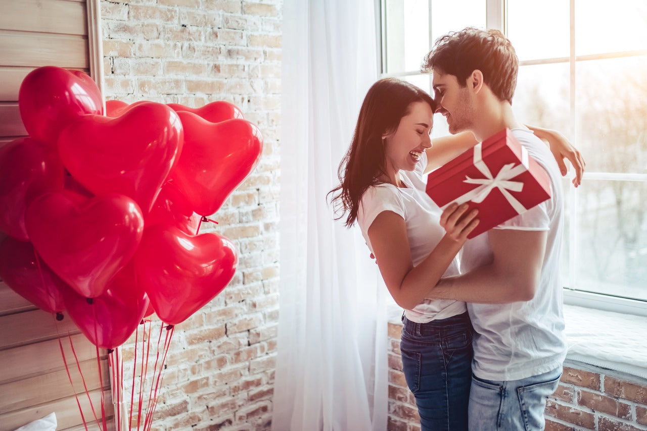 young couple who hug each other a heart shaped balloons
