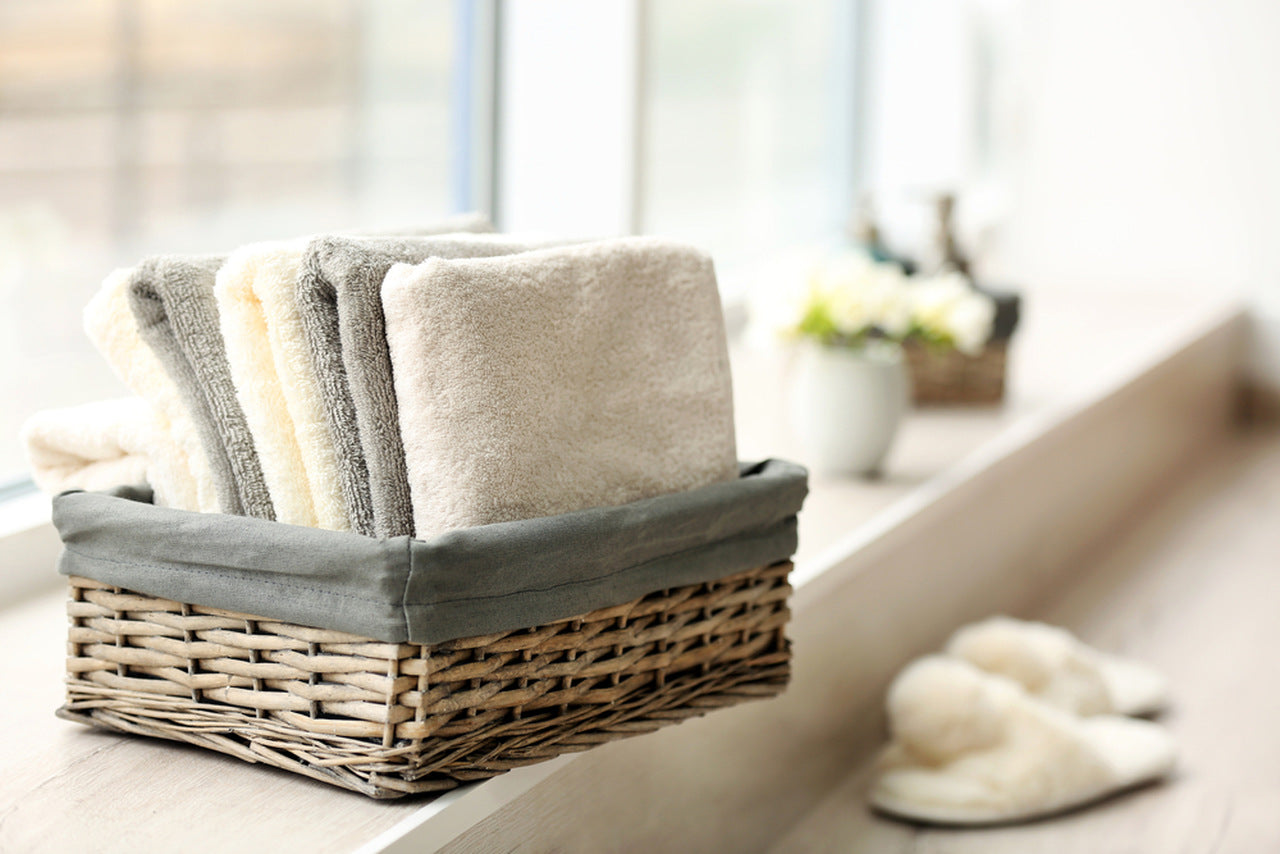 grey and white washcloths in the basket near the window