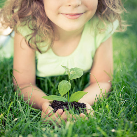 a little girl holding green plant in her hands