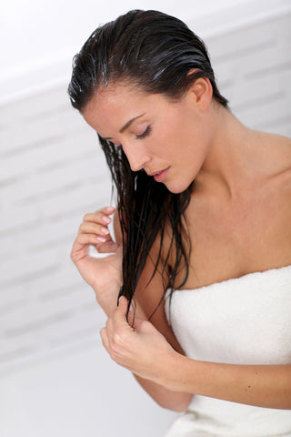a woman, who is wrapped in a towel, applies a hair conditioner to her hairs