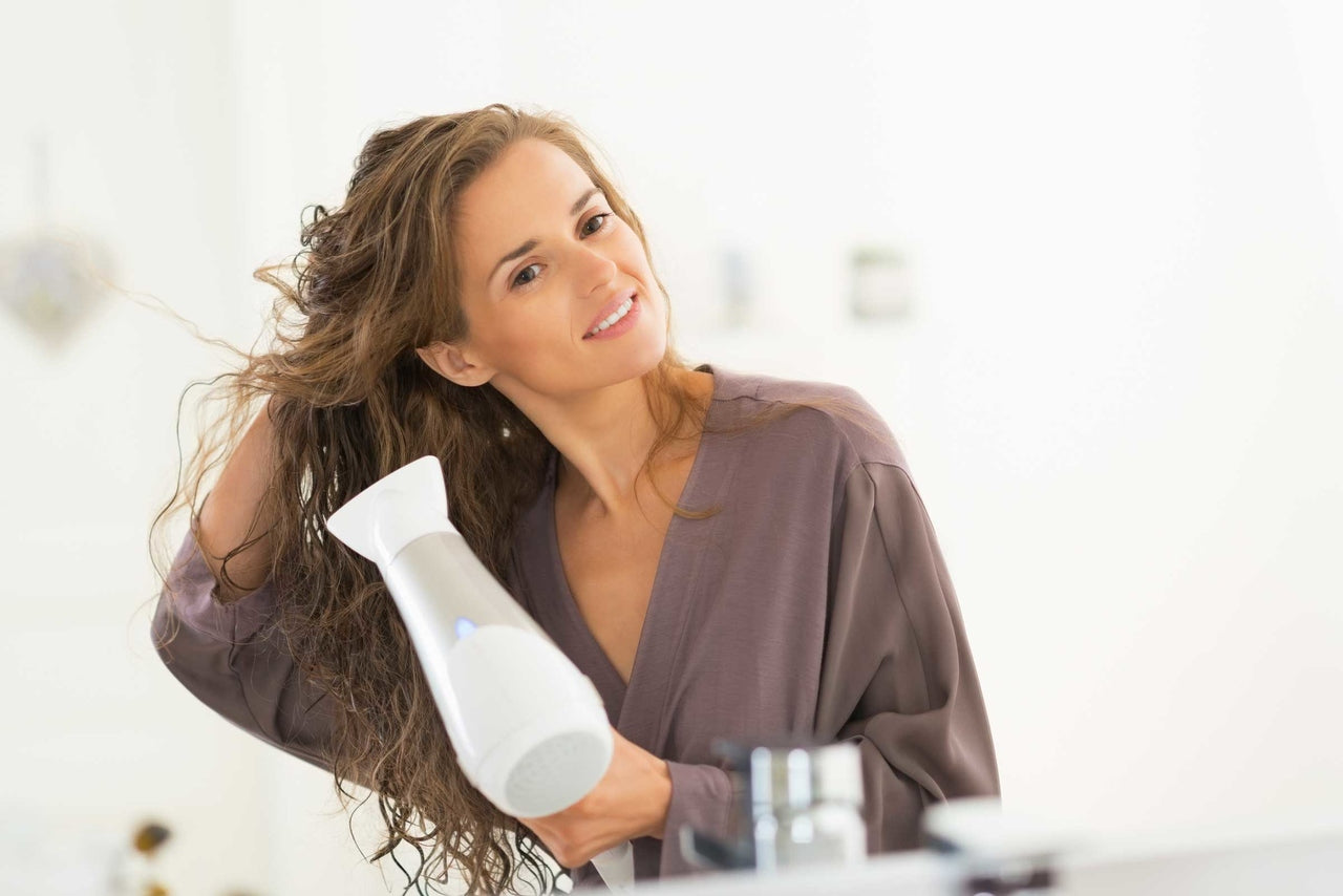 a woman who wears a bathrobe is drying her hairs with a blow drier to know how to dry hair fast