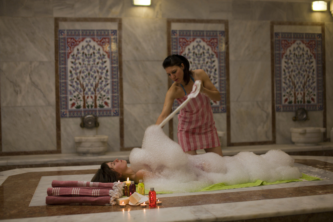 woman bathing with a foam in hammam