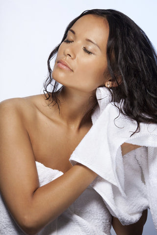 a woman is rubbing her hairs with a towel
