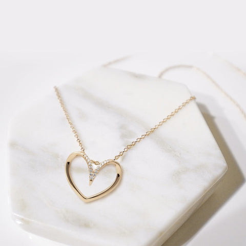 one of the awesome bridesmaid gift ideas is heart shaped necklace on the marble surface