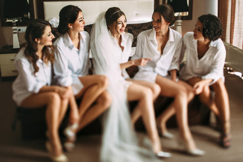girls, who wore white blouses, celebrating bachelorette party in a room