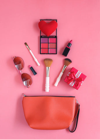 a pink makeup bag and makeup materials such as rouge, blusher, and eyeliner