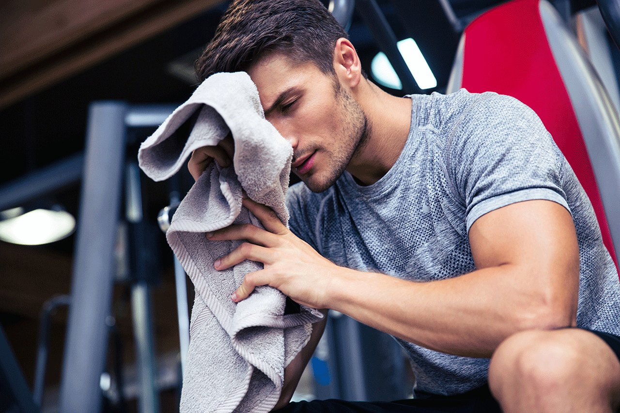 a man, who is sporting at the gym, cleans his sweat with his gray towel