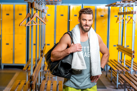 a smiling man in the gym with his best gym towel