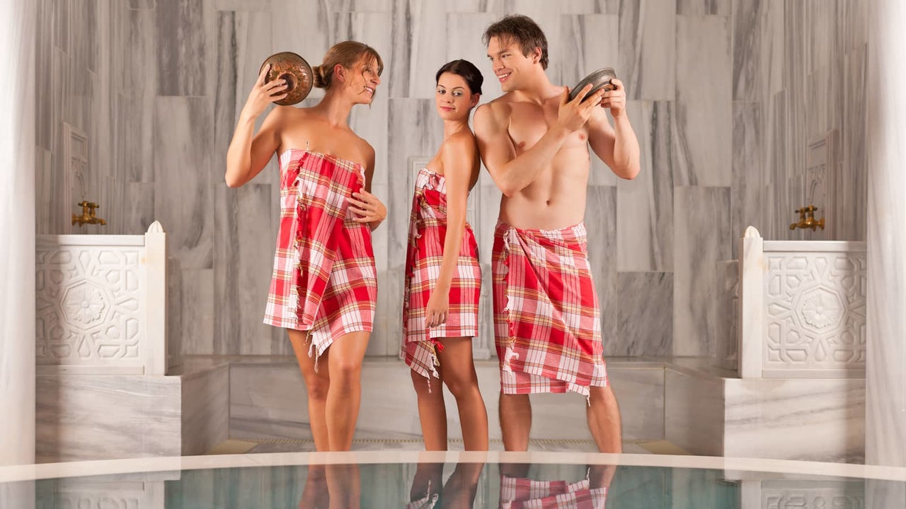2 women and a man who are wrapped in peshtemal towels in Turkish bath