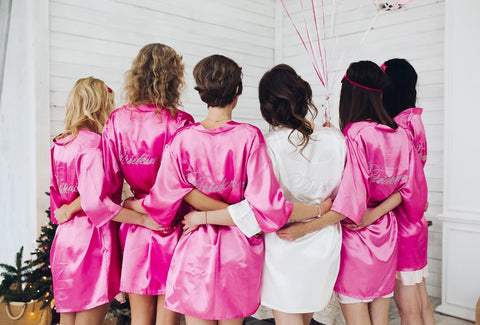 back view of woman friends who wore pink satin robes and hug the bride wore a white satin robe as an answer to the question of what is a bachelorette party