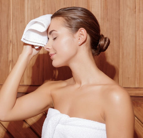 a woman wrapped in a white towel rubbing his face with a white washcloth