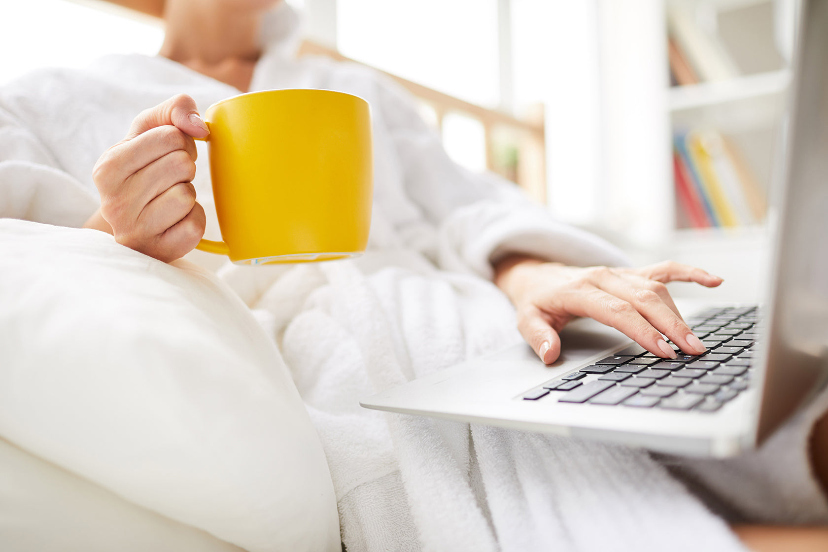a woman in bathrobe who are using laptop
