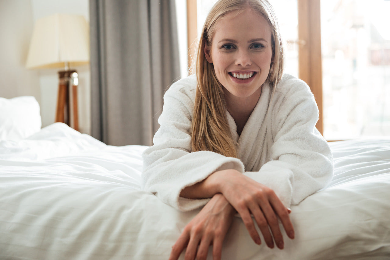 a woman laying in bad with white bathrobe