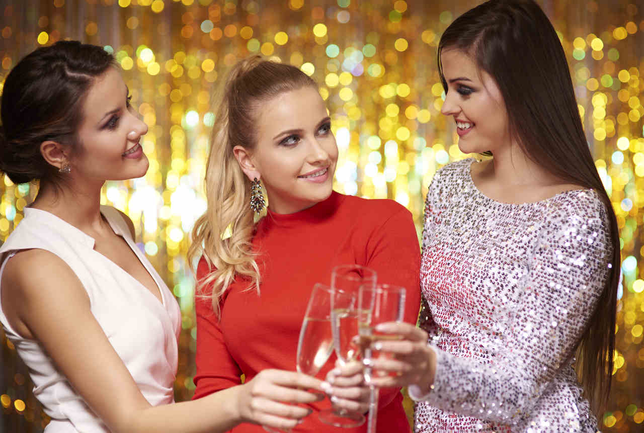 3 elegant dressed women smiling each other