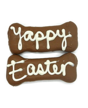 "Bone shaped biscuits, coated in carob with ""Yappy"" & ""Easter"" handwritten in yoghurt."