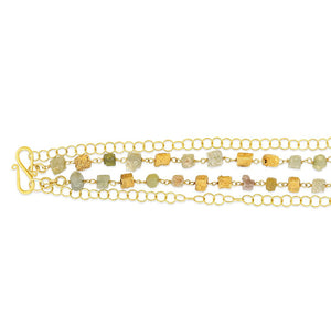 A layered necklace with a circular chain and a textured enriched 18K yellow fine gold squares with square rough diamonds