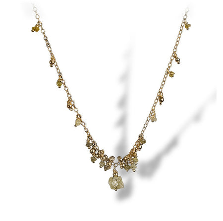 A dainty necklace of textured enriched 18K yellow fine gold beads with rough diamonds