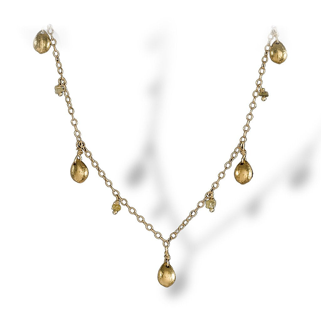 A dainty necklace of textured enriched 18K yellow fine gold teardrops with rough diamonds