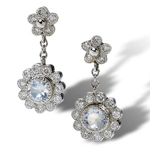 Floral motif daisy earrings in antiquing with diamonds and moonstone dangle from a budding petite daisy