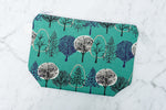 Handmade large makeup bag in a green forest print.