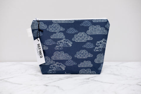 Handmade large makeup bag in a navy blue clouds print.