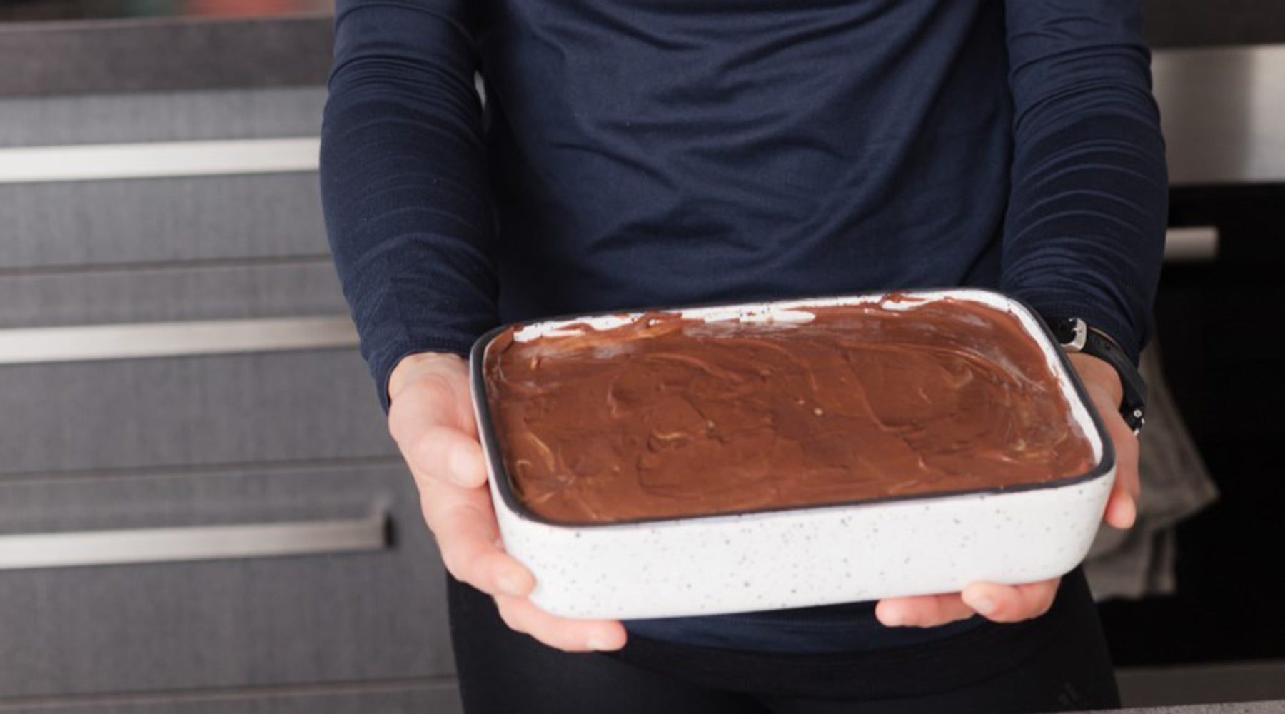 Photo of Megan Craig from Megs and Soph holding a delicious wholefood raw caramel slice.