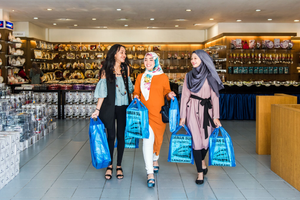 Three ladies walking out of Idaman Suri with the signature blue shopping bags