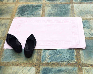 Laid out light pink cotton bath mat by Idaman Suri
