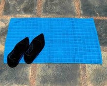 Laid out light blue cotton bath mat by Idaman Suri