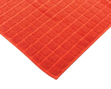 Opened orange cotton bath mat by Idaman Suri