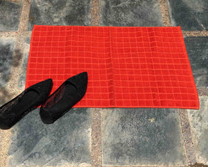 Laid out orange cotton bath mat by Idaman Suri