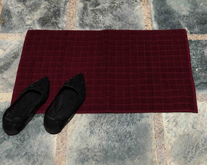 Laid out dark red cotton bath mat by Idaman Suri