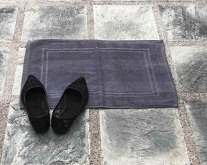 Laid out grey cotton bath mat by Idaman Suri