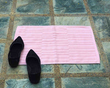 Laid out pink cotton bath mat by Idaman Suri
