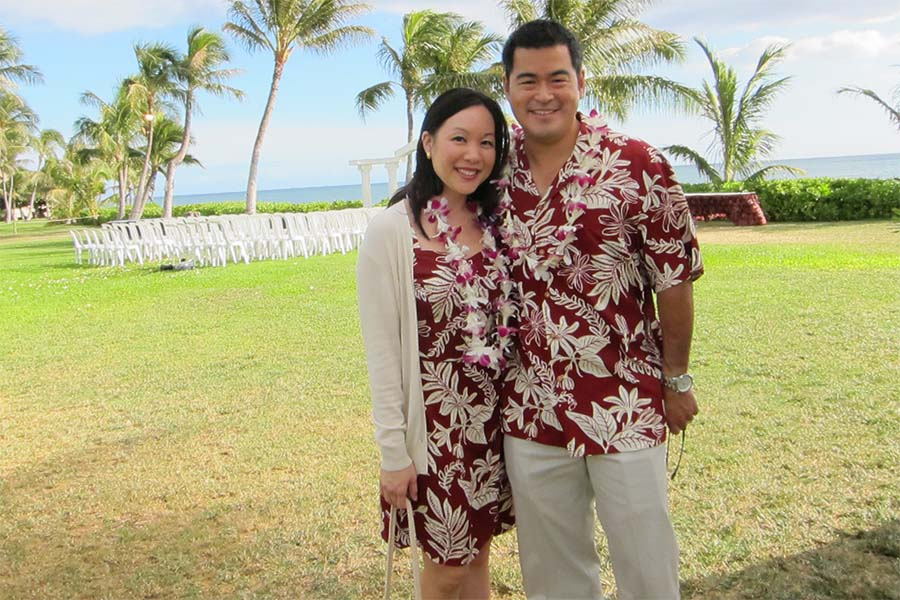 A couple attends a beachside luau wedding in matching aloha shirt and dress. The shirt is untucked.