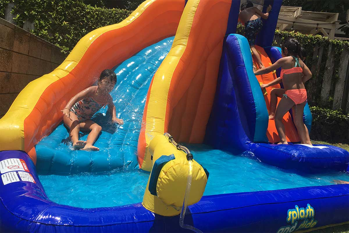 kids playing on an inflatable water slide in the backyard