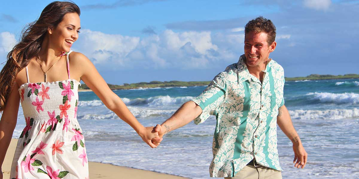 couple enjoying a stroll on the beach in a Hawaiian shirt and dress