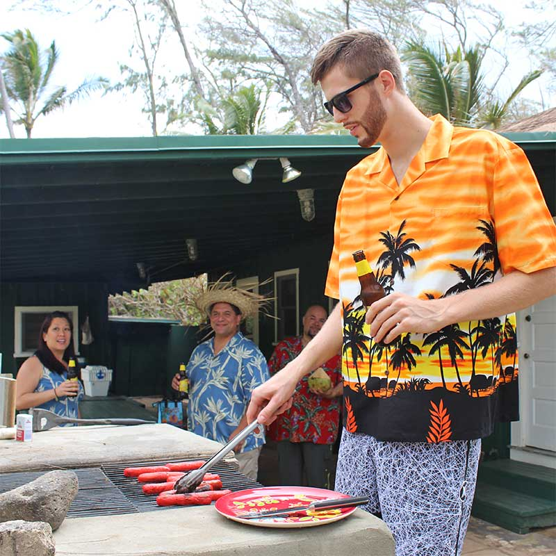 Davis Rozitis grilling hot dogs in an orange Hawaiian shirt and board shorts