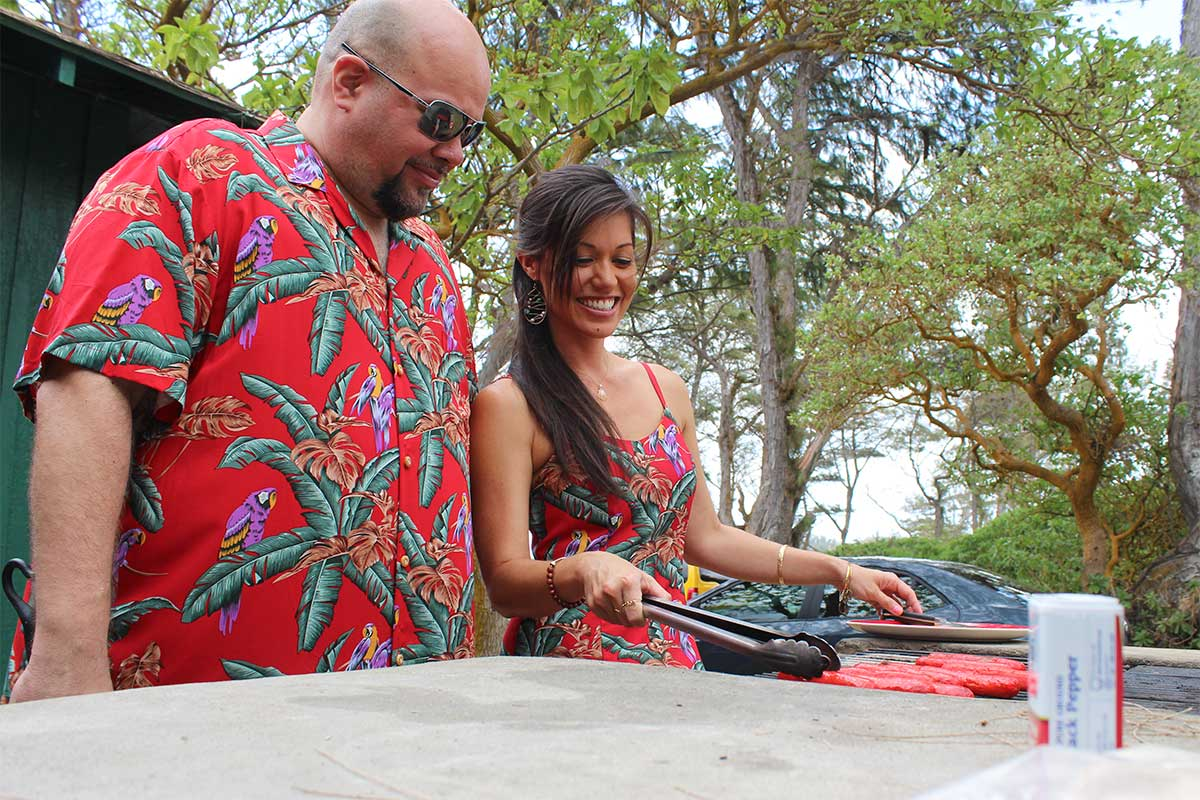 grilling at a beach house in matching Magnum PI Hawaiian shirt and dress