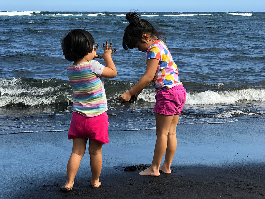 Kids love the black sand at Punaluu Black Sand Beach